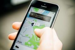 Frau, die auf das UBER-Taxi auf britischer Straße mit messa wartet Lizenzfreie Stockfotos