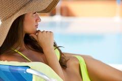Frau, die auf deckchair durch Schwimmbad liegt Lizenzfreie Stockbilder