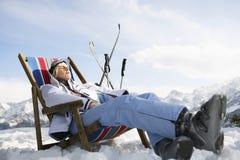 Frau, die auf Deckchair in Snowy-Bergen stillsteht Stockfotos