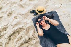 Frau, die auf Decke auf Sand in der Schwimmenklage legt Lizenzfreies Stockfoto