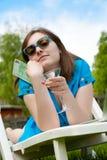 Frau, die auf dem Aufenthaltsraum liegt und ein Weinglas anhält lizenzfreie stockfotos