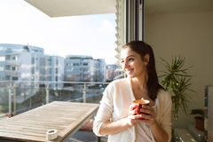 Frau, die auf dem Balkon hält Tasse Kaffee oder Tee sich entspannt Stockfotografie