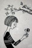 Frau, die auf dem Baum in der Hand hält Vogel sitzt Lizenzfreie Stockfotografie