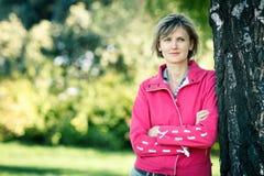 Frau, die auf dem Baumstamm sich lehnt Lizenzfreies Stockfoto