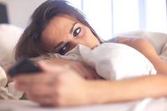 Frau, die auf dem Bett überprüft ihr Telefon liegt Stockfotos