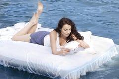 Frau, die auf dem Bett im Meer liegt Lizenzfreie Stockfotografie