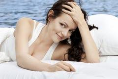 Frau, die auf dem Bett im Meer liegt Stockbilder