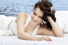 Frau, die auf dem Bett im Meer liegt Lizenzfreie Stockbilder