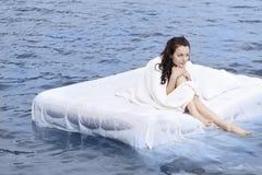 Frau, die auf dem Bett im Meer schläft Stockfotos