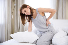 Frau, die auf dem Bett mit Rückenschmerzen sitzt stockfotografie