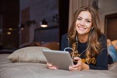 Frau, die auf dem Bett mit Tablet-Computer liegt Stockfotografie