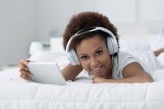 Frau, die auf dem Bett sich entspannt lizenzfreie stockfotos