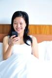 Frau, die auf dem Bett unter Verwendung ihres Smartphone sitzt Stockbild