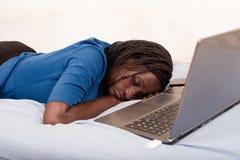 Frau, die auf dem Bett vor einem Laptop schläft stockbild