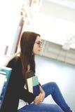 Frau, die auf dem Boden in der Bibliothek sitzt Lizenzfreies Stockbild