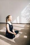 Frau, die auf dem Boden in der Haltung der Meditation sitzt Stockbild