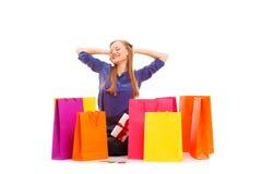 Frau, die auf dem Boden hinter Einkaufstaschen sitzt Lizenzfreie Stockfotos