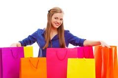 Frau, die auf dem Boden hinter Einkaufstaschen sitzt Lizenzfreie Stockbilder
