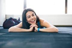 Frau, die auf dem Boden liegt und ihre Zunge zeigt Lizenzfreie Stockfotografie