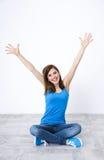 Frau, die auf dem Boden mit den angehobenen Händen oben sitzt Lizenzfreie Stockfotografie