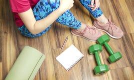 Frau, die auf dem Boden nach execrises sitzt, den Trainingsplan stillsteht und cheking stockbilder