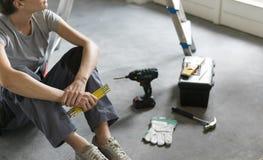 Frau, die auf dem Boden sitzt und eine Haupterneuerung plant stockfotografie