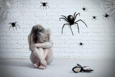 Frau, die auf dem Boden sitzt und auf eingebildeter Spinne schaut lizenzfreies stockfoto
