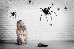 Frau, die auf dem Boden sitzt und auf eingebildeter Spinne schaut lizenzfreie stockfotos