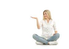 Frau, die auf dem Boden sitzt und mit ihrem Finger zeigt Lizenzfreies Stockfoto