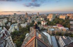 Frau, die auf dem Dach auf dem modernen Gebäude in Kiew, Ukraine seatting ist Lizenzfreies Stockfoto