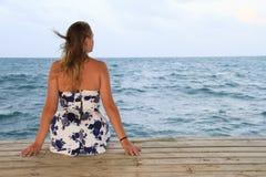 Frau, die auf dem Dock, Ozean betrachtend sitzt Stockbild