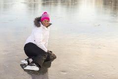 Frau, die auf dem Eislauf sitzt Lizenzfreies Stockbild