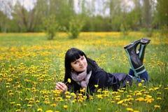 Frau, die auf dem Feld mit Löwenzahn liegt Lizenzfreies Stockfoto
