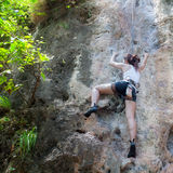 Frau, die auf dem Felsen klettert Stockfotos