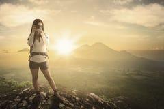 Frau, die auf dem Felsen mit einer Kamera steht Stockfotos
