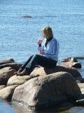 Frau, die auf dem Felsen sitzt Lizenzfreies Stockfoto
