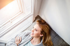 Frau, die auf dem Fensterbrett, schauend aus Fenster heraus liegt Stockfotografie