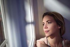 Frau, die auf dem Fensterbrett, schauend aus Fenster heraus sitzt Stockfoto