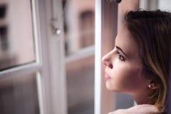 Frau, die auf dem Fensterbrett, schauend aus Fenster heraus sitzt Lizenzfreie Stockfotografie