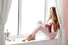 Frau, die auf dem Fensterbrett sitzt Lizenzfreie Stockfotos