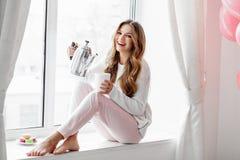 Frau, die auf dem Fensterbrett und auslaufende der Tee oder der Kaffee vom Kessel sitzt Stockbild