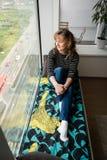 Frau, die auf dem Fensterleistenbett sitzt Stockfoto