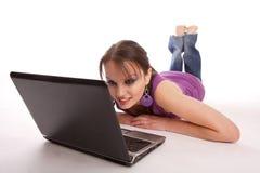 Frau, die auf dem Fußboden mit Laptop liegt Stockfotografie