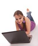 Frau, die auf dem Fußboden mit Laptop liegt Stockbilder