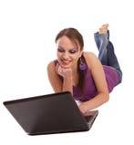 Frau, die auf dem Fußboden mit Laptop liegt Lizenzfreies Stockbild
