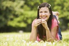 Frau, die auf dem Gebiet der Gänseblümchen sich entspannt Stockbilder