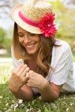 Frau, die auf dem Gebiet der Sommer-Blumen liegt Stockfotos