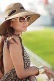Frau, die auf dem Geländer sich lehnt Lizenzfreie Stockfotografie