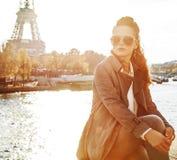 Frau, die auf dem Geländer sitzt und Abstand in Paris untersucht stockfotografie