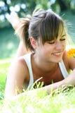 Frau, die auf dem Gras, lächelnd liegt Stockfotografie